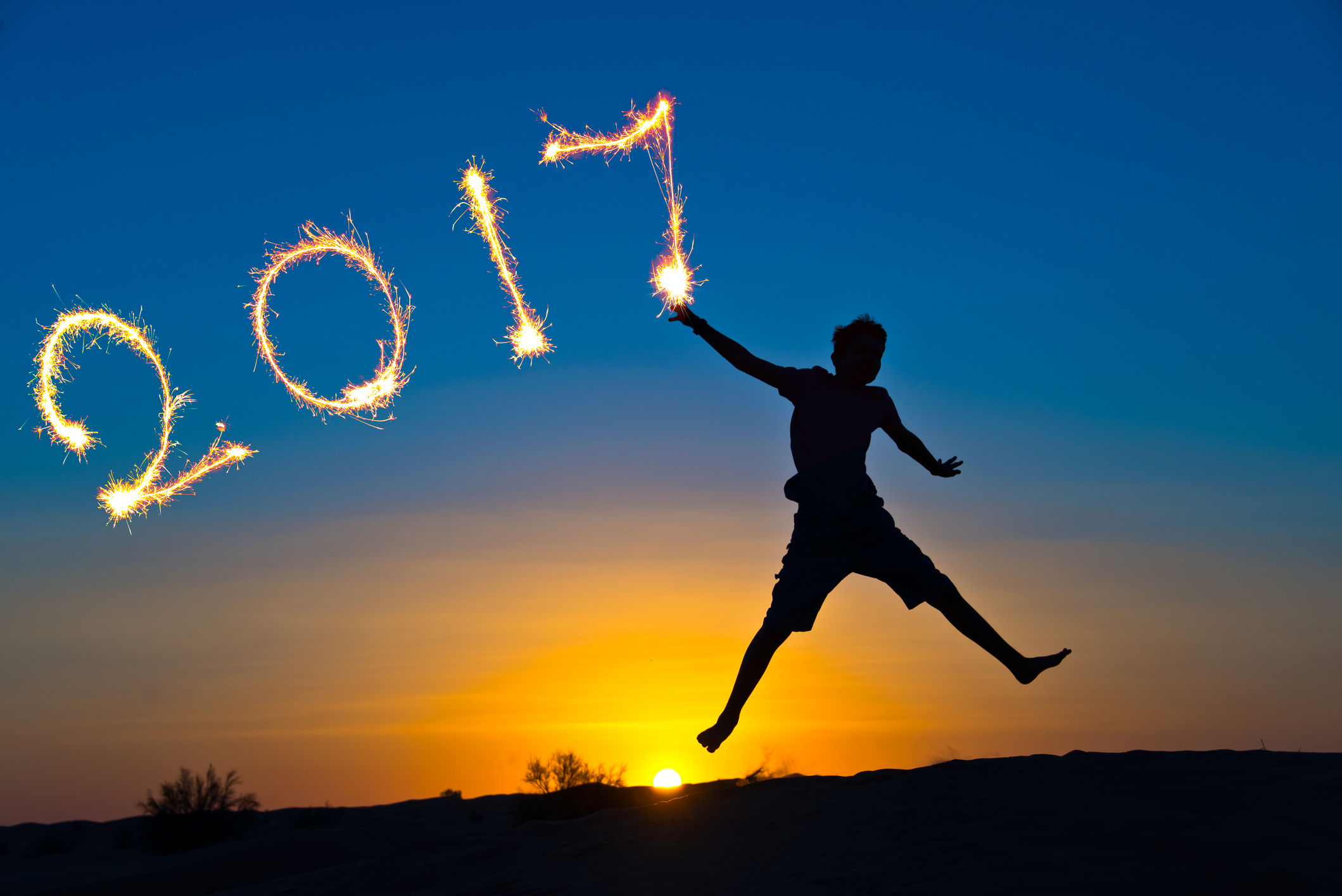 year 2017 written with sparkles, silhouette of a boy jumping