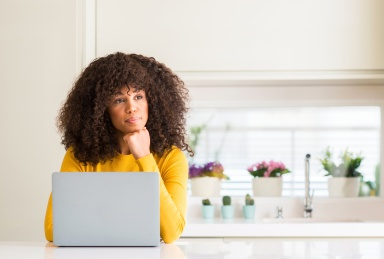 African american woman using computer laptop at kitchen serious face thinking about question, very confused idea